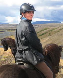 Islandsrejser arrangerer din rejse til Færøerne. Her er Mette Viberg fra FÆRØERNEREJSER siddende på en islands hest