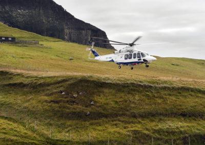 Helikopter lander på Mykines på kør-selv ferie, bilferie og grupperejser med FÆRØERNEREJSER